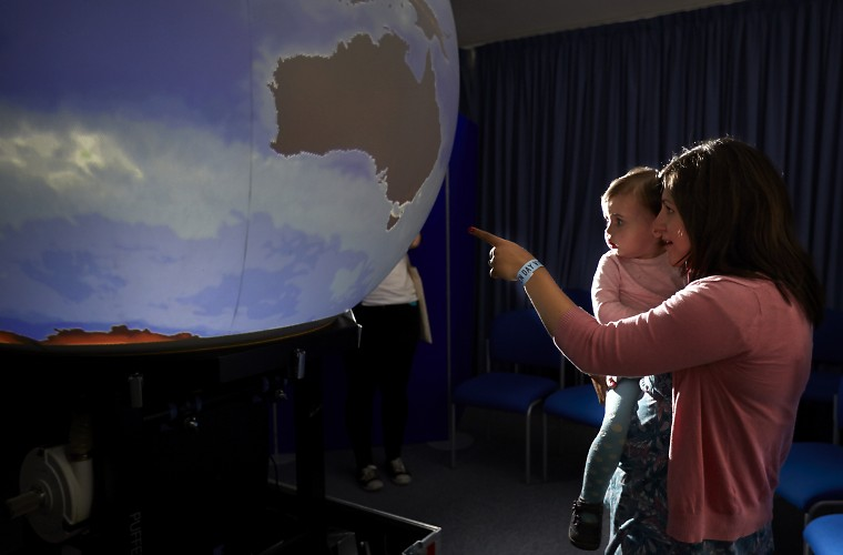 Woman with baby looking at large Earth globe